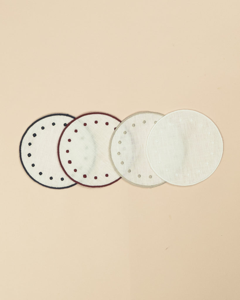 Set of four round side plates, all in white but with blue, bordeaux, beige and white colours on the embroidered edge and on the embroidered dots along the edge