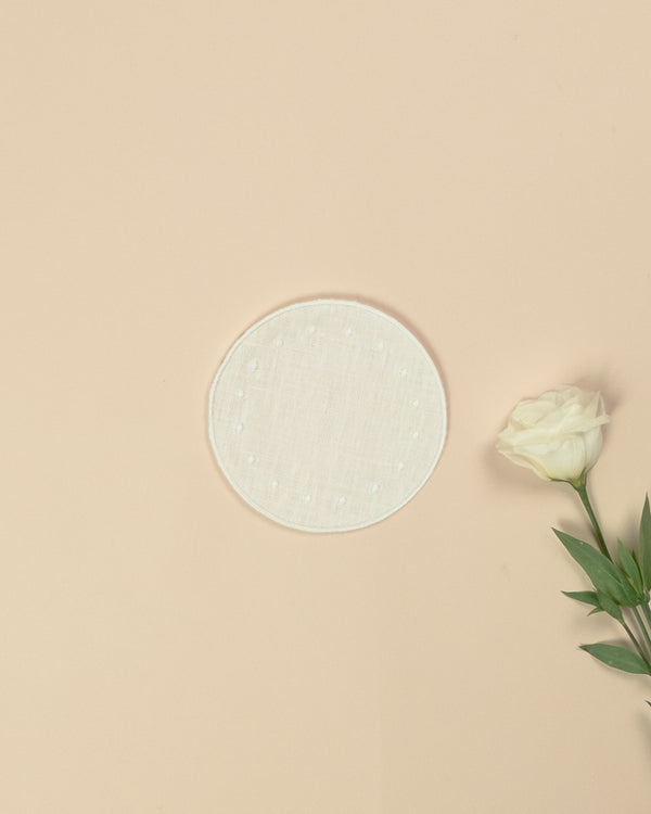 White round side plate with embroidered white borders and white dots, next to a white rose