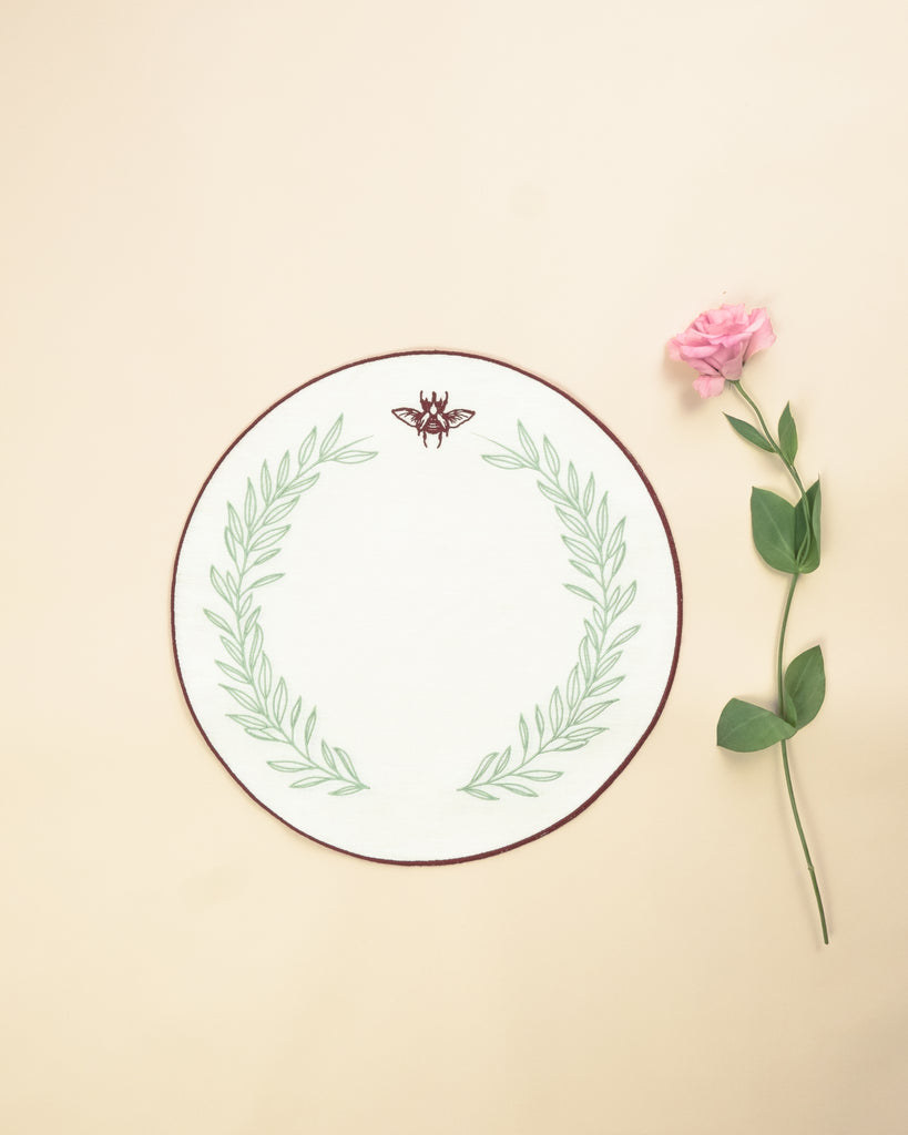 Round placemat in white with embroidered bordeaux border and a bordeaux scarab and green foliage embroidered