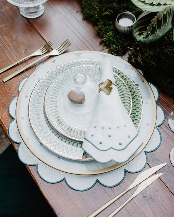 Festive table setting with matching napkin and placemat, both with green embroidered borders and embroidered green dot details