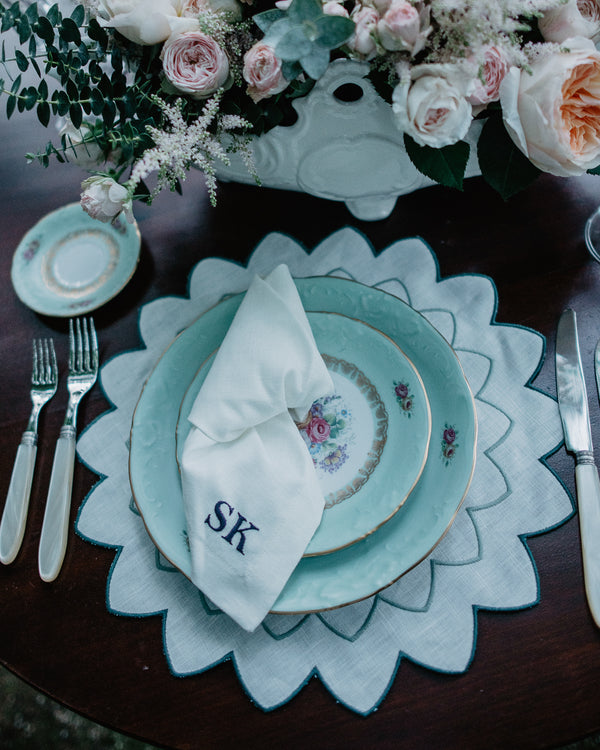 Table Setting with Napkin with embroidered initials on top of a blue Plate standing on a star shaped embroidered placemat