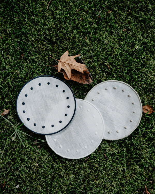 Set of three round side plates in a lawn, all in white but with blue, beige and white colours on the embroidered edge and on the embroidered dots along the edge