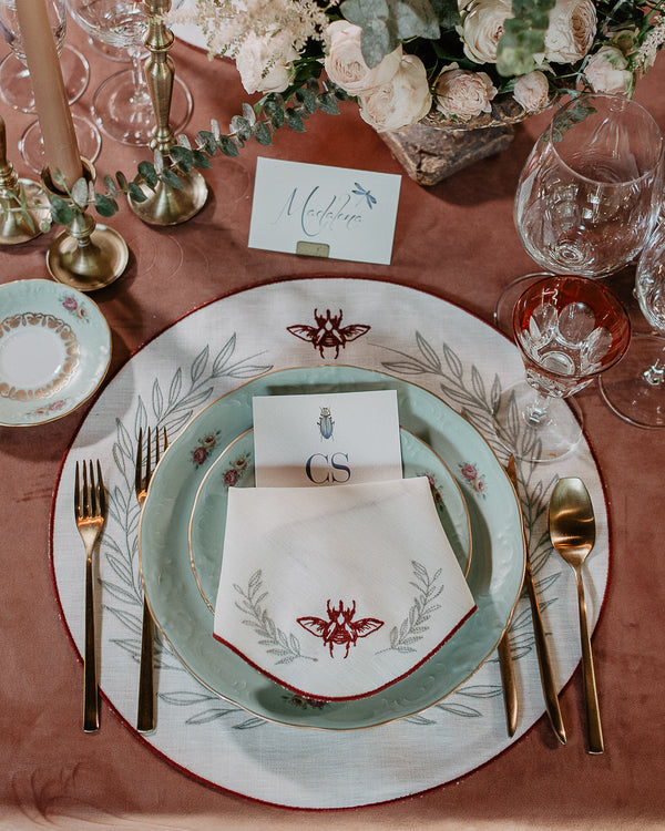 Festive table setting with matching napkin and placemat, both with bordeaux embroidered borders, a bordeaux embroidered scarab and embroidered green foliage
