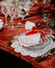 White napkin with bordeaux embroidered borders and details, envolved in a red ribbon, stands on top of a flower-themed ceramic plate placed on top of a flower-shaped placemat matching the napkin embroideries