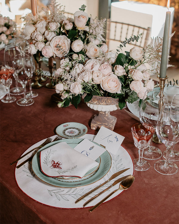 Flowery table setting, with a matching set of napkins and placemats in white, with bordeaux embroidered borders, and a bordeaux scarab and green foliage embroidered in each