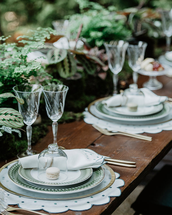 Festive table setting with a green theme with matching napkin and placemat, both with green embroidered borders and embroidered green dots details