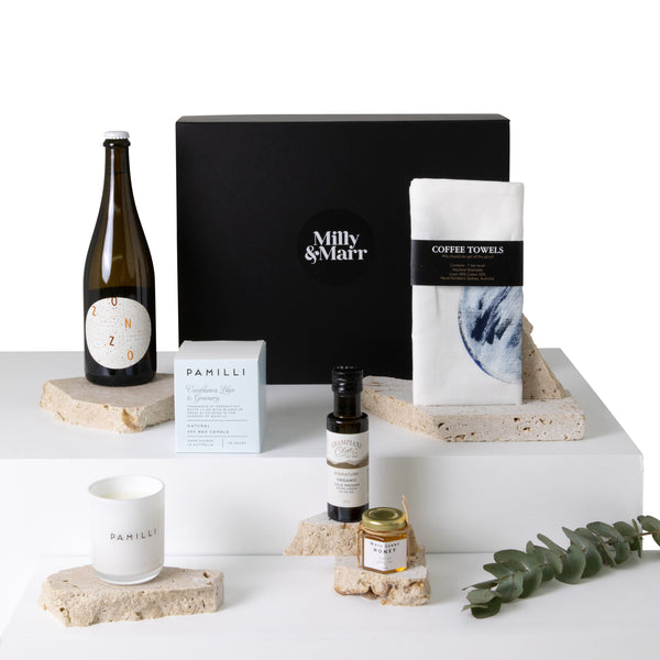 the milly and marr housewarming gift box selection laid out including zonzo estate prosecco, pamilli soy wax candle, coffee towels hand printed tea towel, maya sunny honey 100ml jar, grampians olive oil in a black magnetic keepsake box
