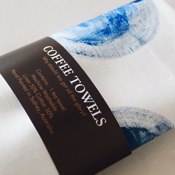 50% linen and 50% cotton tea towel with large blue hand painted circles on a white background