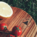a close up pf the board in use with a lemon and fresh tomatoes on top, showing the logo which is marked into the board and reads quality timber products