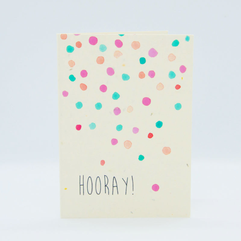 the hello petal horray birthday card made of recycled plantable paper with pink orange and green confetti spots on the front with the words HOORAY underneath