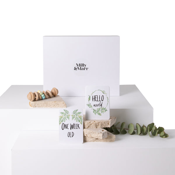 Milly and Marr white magnetic gift box inclusive of a tiny moons vintage rattle with 4 wooden chewable safe circles and silicone beads. Vanda baby fern milestone baby cards.