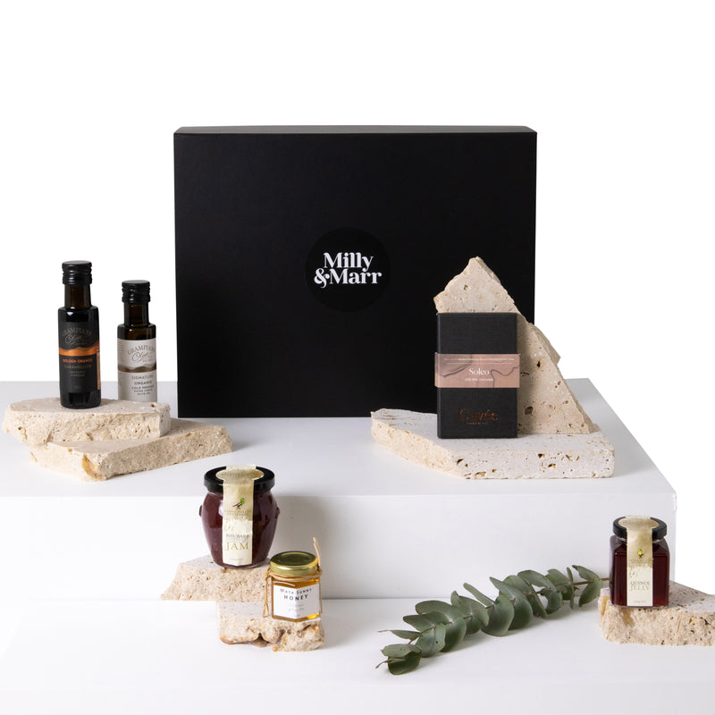 Milly & Marr Australian Produce gift box featuring a black magnetic keepsake box. Grampians olive oil and balsamic oil, cuvee chocolate, raspberry and rhubard jam, maya honey and yarra valley quince paste in a jar.
