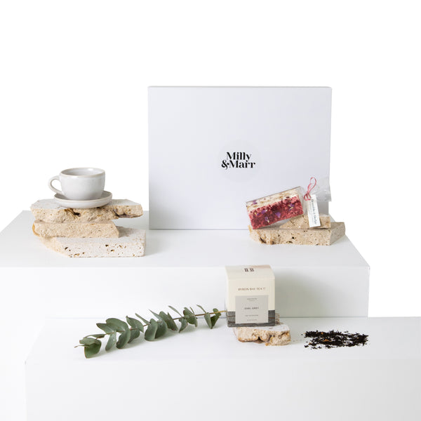 a coast coloured ceramic teacup styled with australian natives, a box of byron bay tea earl grey with tea leaves scattered, and the beautiful dried raspberry adorned australian nougat from bramble and bramble