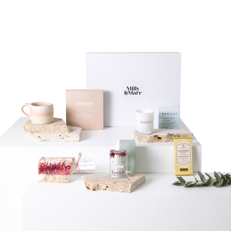 the milly and marr set the mood gift box laid out showing a pastel pink ceramix mug, a bath brew tea bag, beautifully presented handmade nougat, pamilli candle, peggy sue body oil and winebar coconut and rum choicolate bar