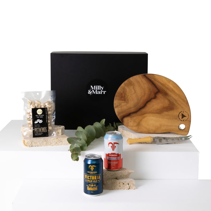 the summer days corporate mens gift box from milly and marr featuring a cheese board and knife and locally created beers and pistachios in a black magnetic keep sake box
