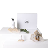 a gift box with magnetic keepsake box in white with black milly & marr text on the front, the aspar spa botanical body wash and lip balm in white bottles and the tiny moons wooden and black beaded necklace