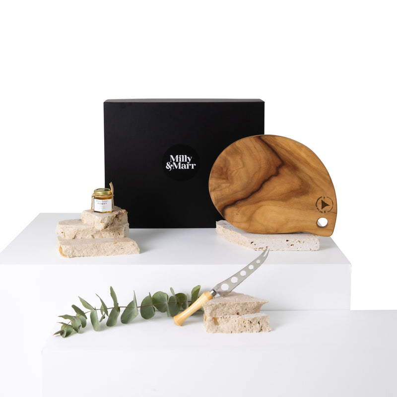 Milly & Marr australian made corporate gift box presented in a black magnetic keepsake gift box. includes maya sunny honey glass jar with wooden server, camphour laurel tear shapes cheese board and huon pine serated cheese knive with 5 holes