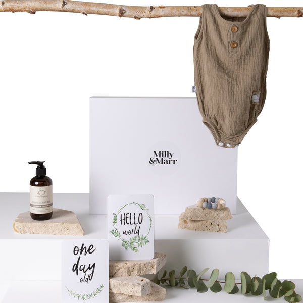 welcome little one gift box laid out showing the mocha organic romper, indera trading silicone teether and vanda baby milestone cards saying one day old and hello world. packaged in a white magnetic keepsake gift box
