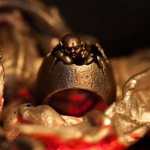 Hand sculpted silver signet ring shaped like a cracked egg with miniature demon peering out. Handmade by Damian Regan