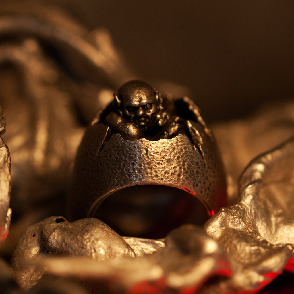 Hand sculpted miniature demon sitting inside cracked egg signet ring. Handmade by Damian Regan.