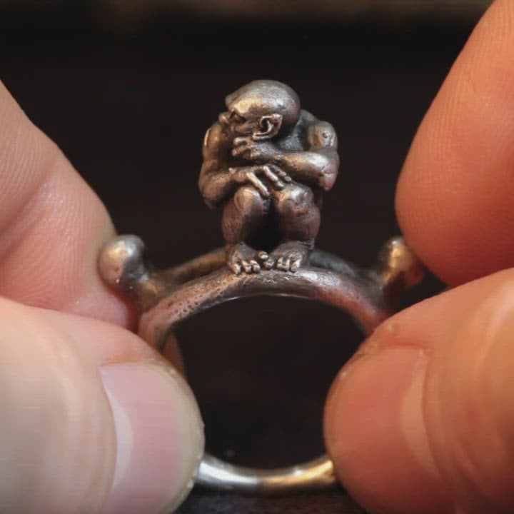 Miniature demon sitting upon silver bone ring band, hand sculpted by Damian Regan