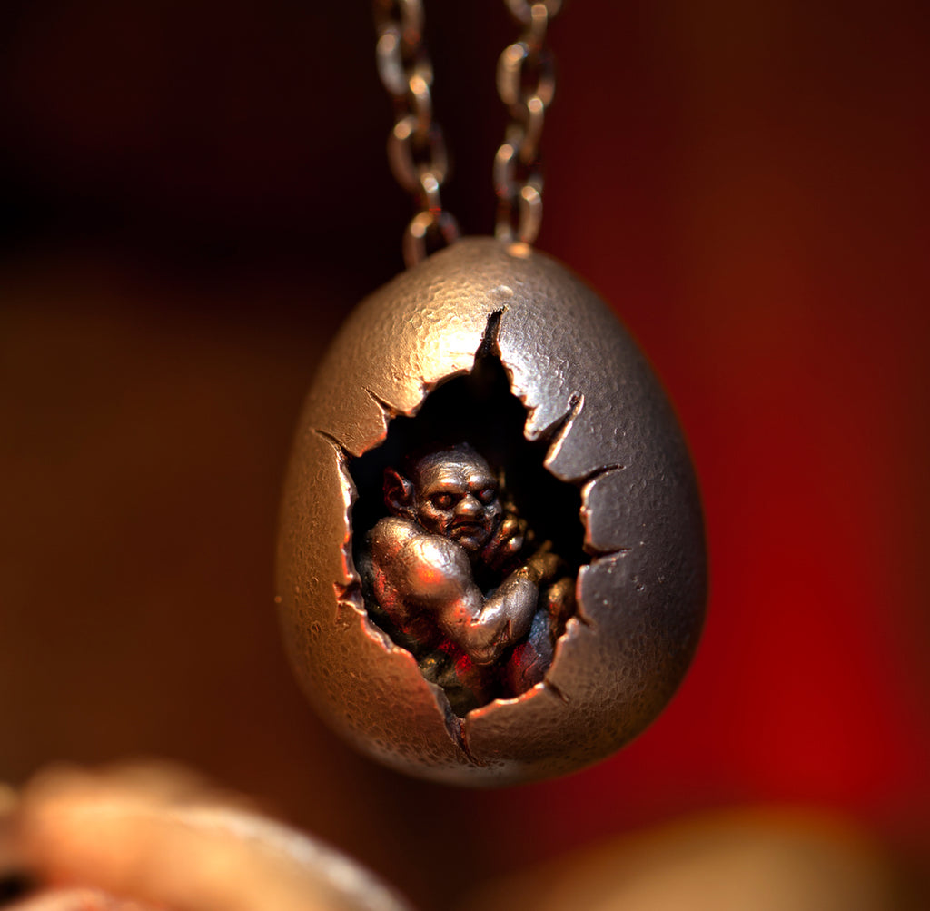Hand sculpted miniature demon sitting inside cracked egg. Handmade by Damian Regan.