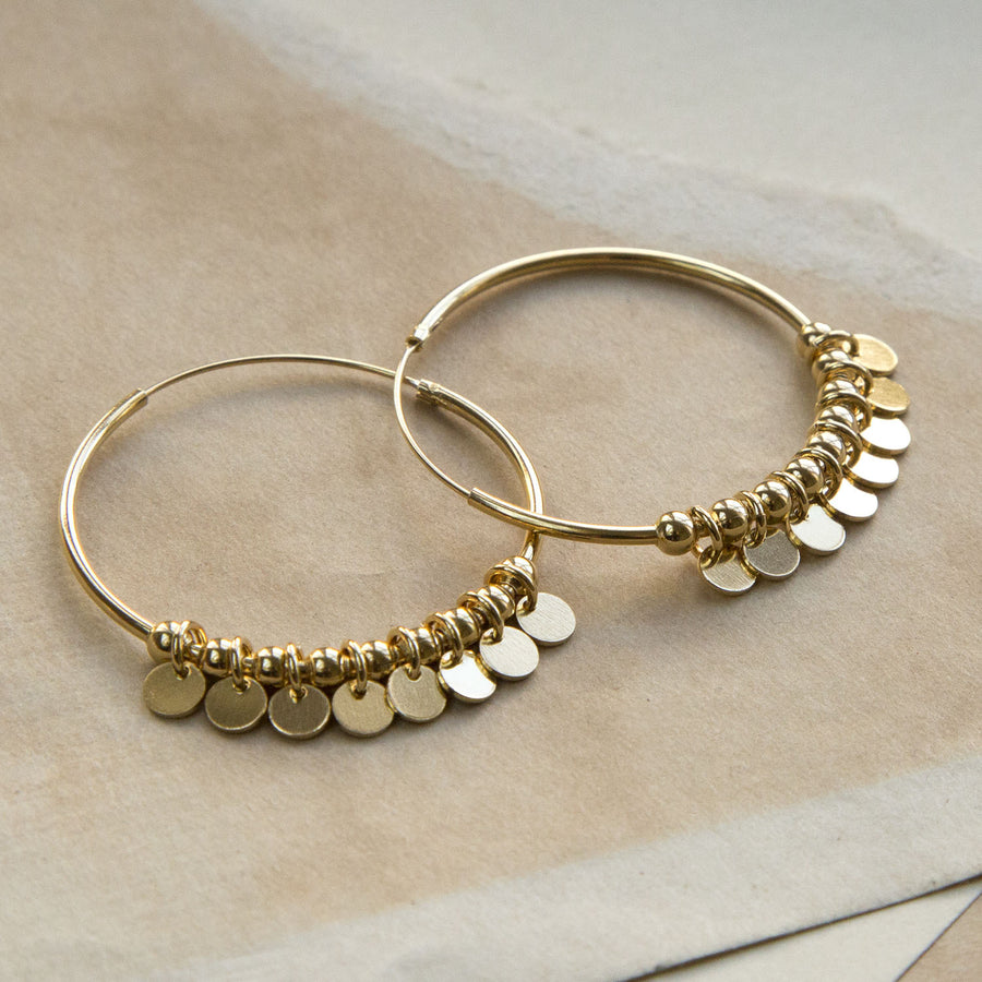 Gold Hoops with sequin detail on a ripped, sandy coloured paper background