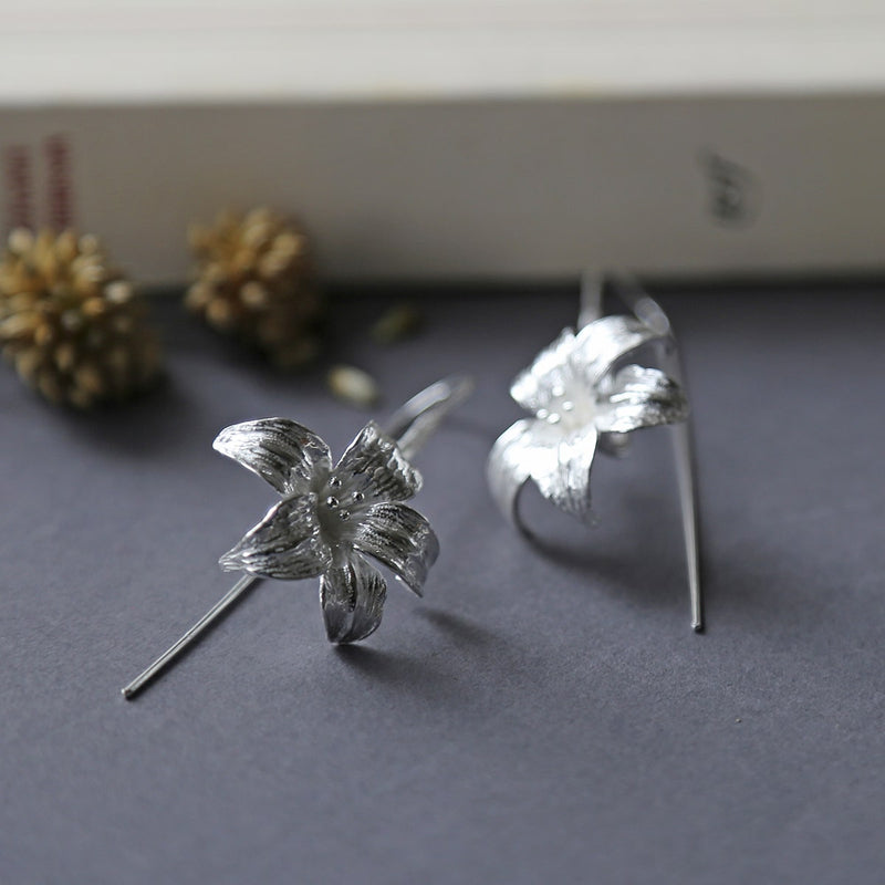 Large silver lily earrings featuring a long silver stem threaded through the ear