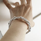 A twisted bubble silver bracelet with a lobster on woman's wrist with a white background and shadows being cast
