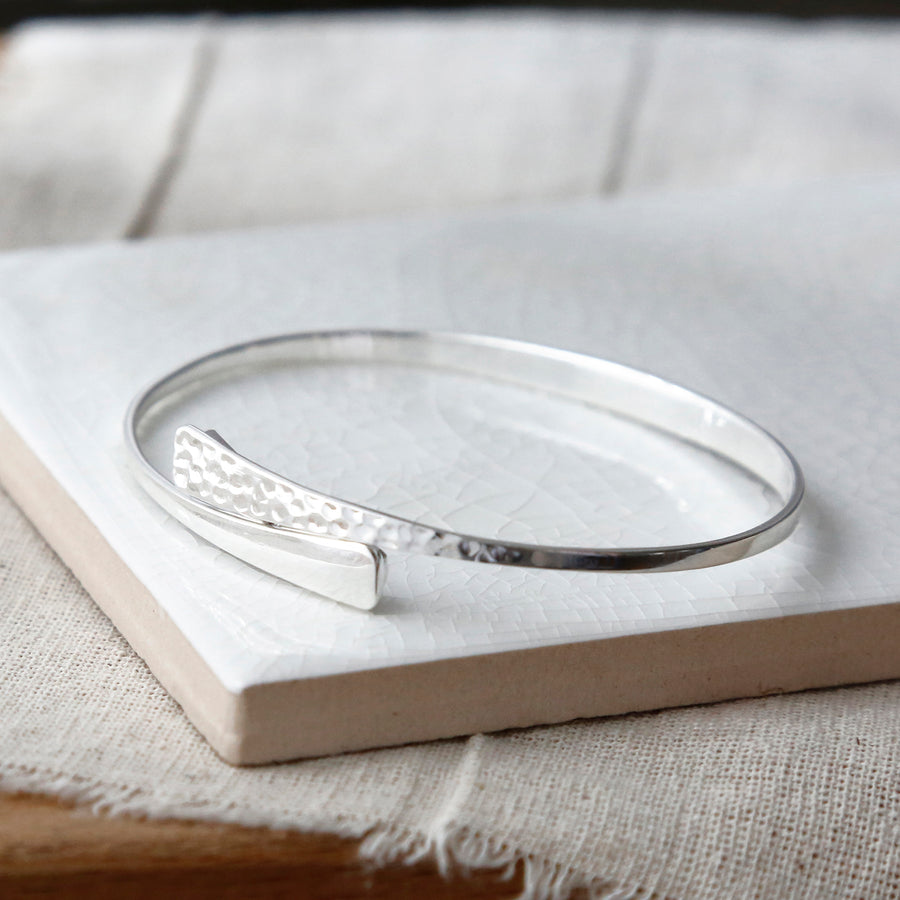 Sterling silver hidden heart bangle on tile showing hammered texture