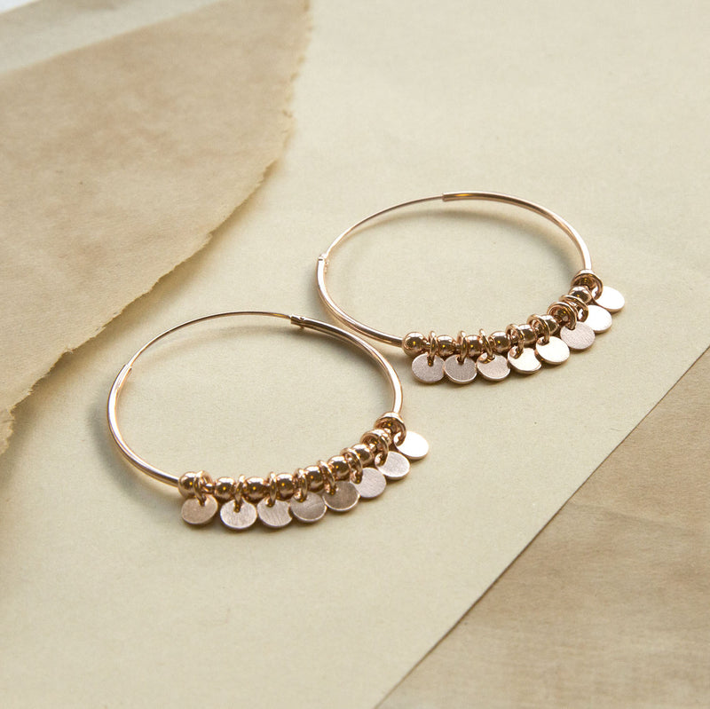 Rose Gold Hoops with sequin style detail, on a sand coloured paper background