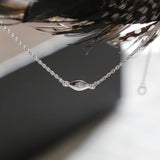 Sterling silver delicate rhombus necklace held up to light