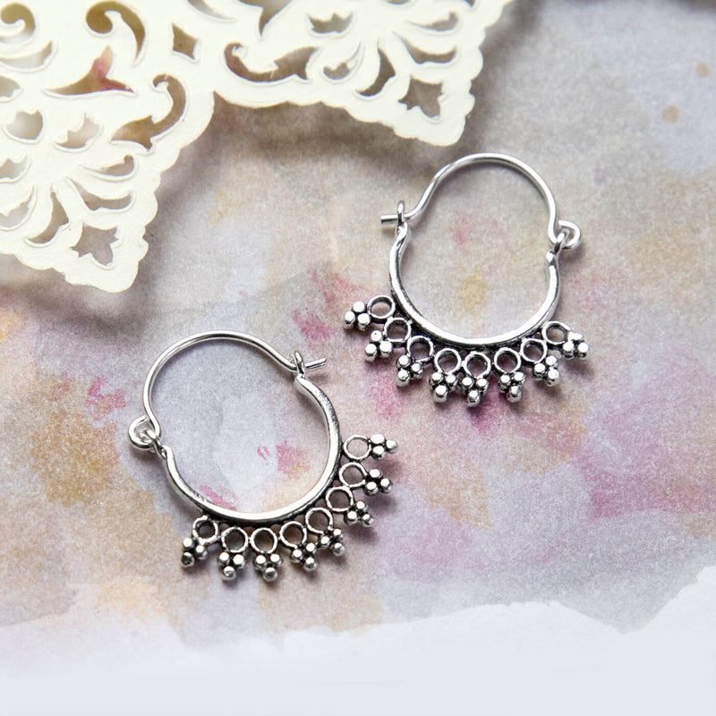 Sterling Silver Temple Hoops Placed on a Pink and yellow watercolour paint background with Cream paper cut out details