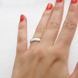 Polished sterling silver friendship ring on model's finger.