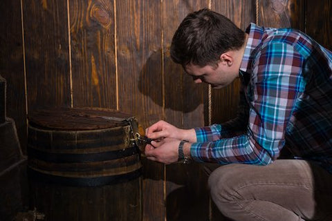 A young man is inspecting a locked box in an escape room