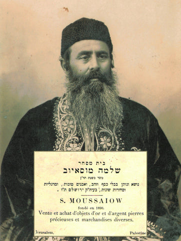 Rabbi Shlomo Moussaieff in traditional Jewish Bukharian dress, with a copy of his business card.