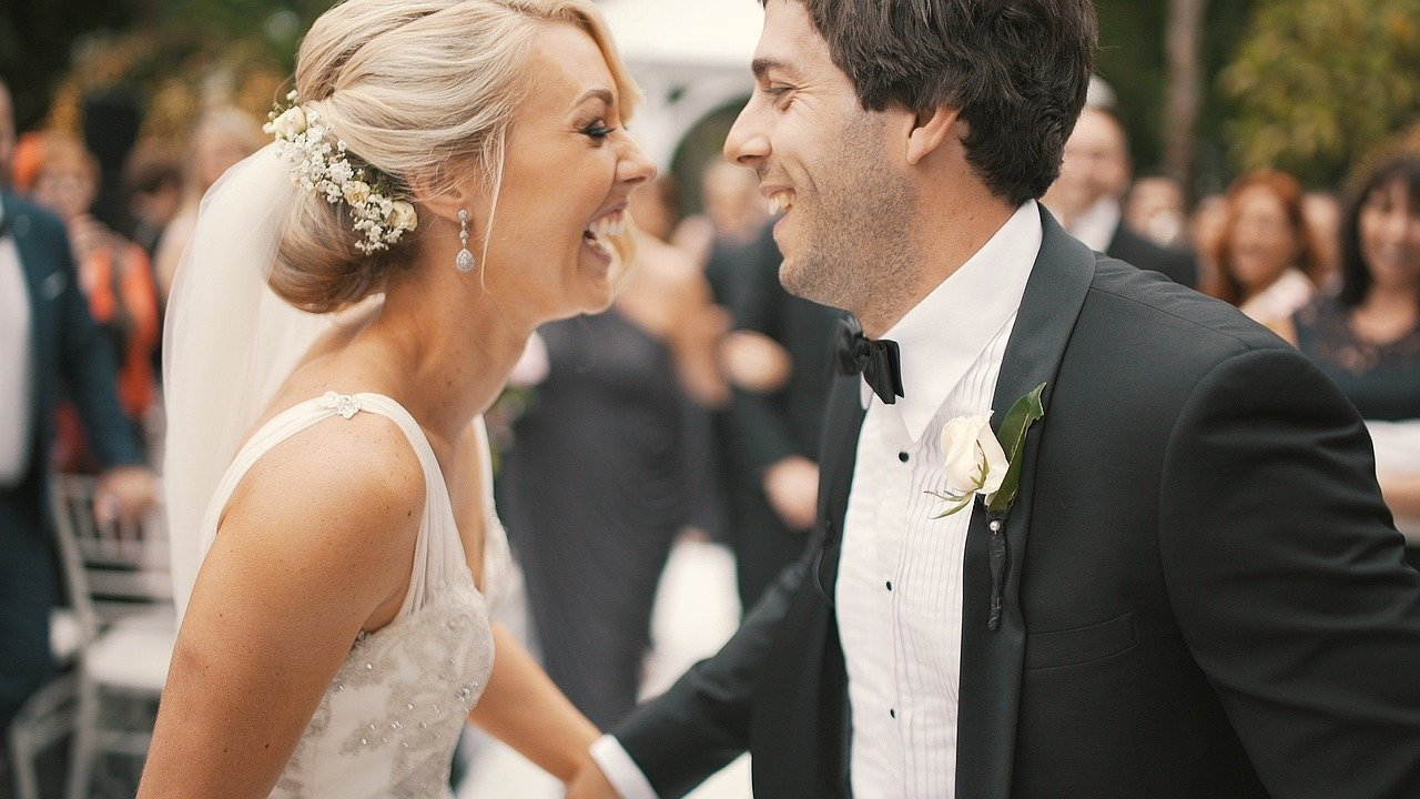 happy bride in floral lace spring wedding gown smiling with her groom