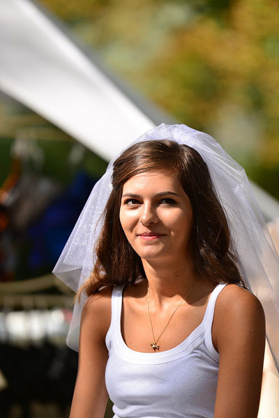 smiling woman in white tank top models shoulder wedding veil length