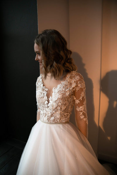 Tulle wedding dress Daffi with long sleeves. 3D flowers lace on bodies. A line skirt with train.  V neck. Bittons back with nude tulle. - oliviabottega