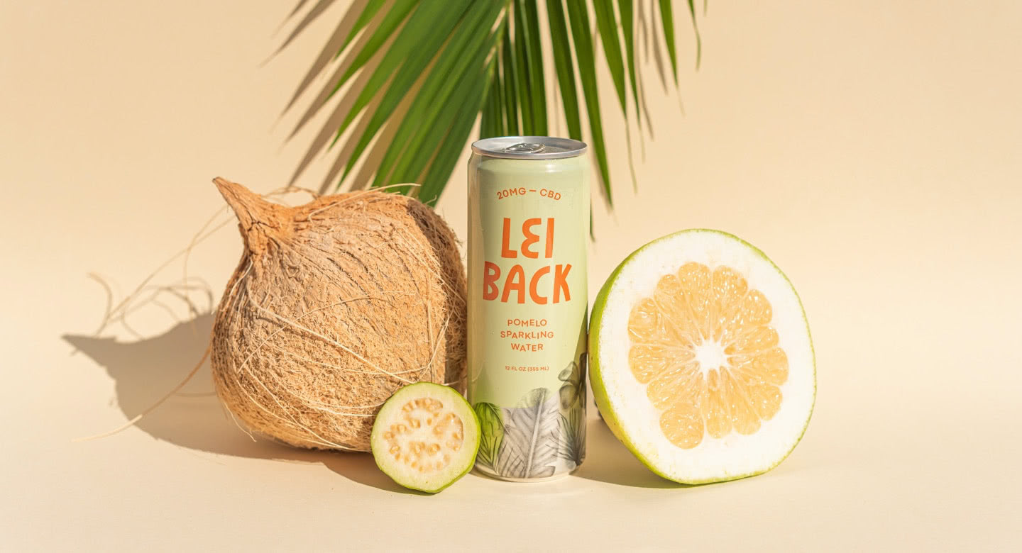 A can of Pomelo Sparkling Water with a coconut and a pomelo