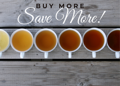 Text reads Buy More Save, grey wooden background, 6 cups of different color teas