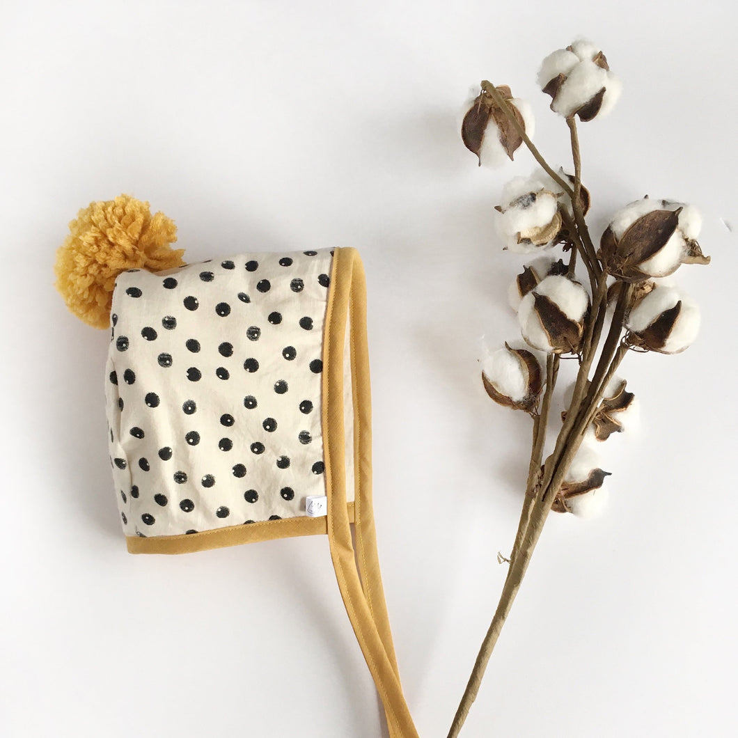 Black and Cream Spotty Winter Bonnet with Mustard Binding and Pom Pom