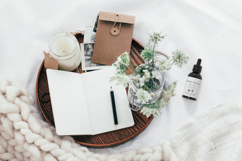 Fender's Blue Hemp Oil Drops with Notebook and Other Items On Bed