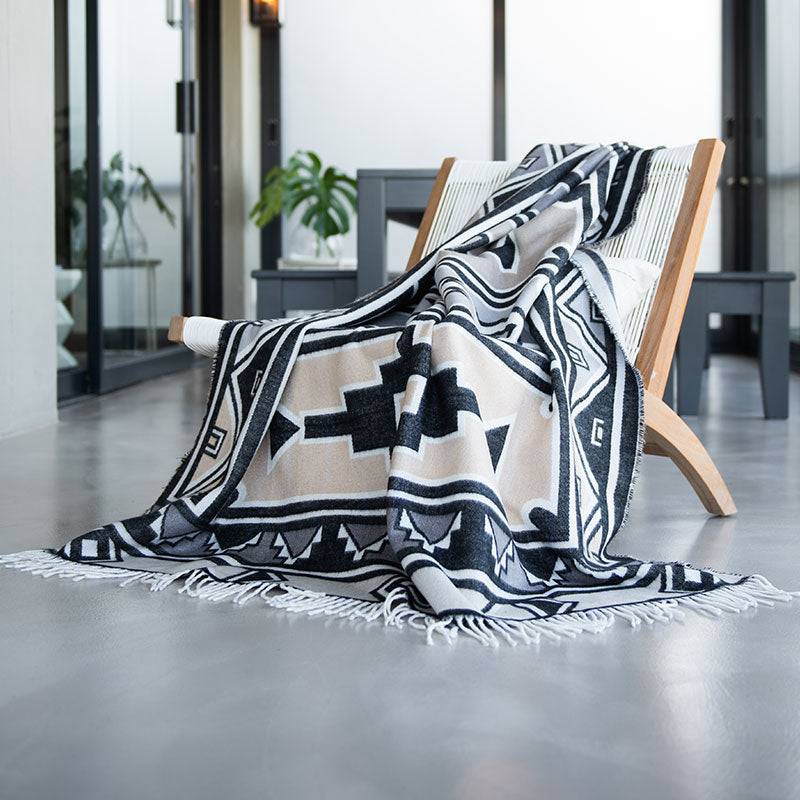 African style blanket laying drapped of contemporary modern chair in modern house