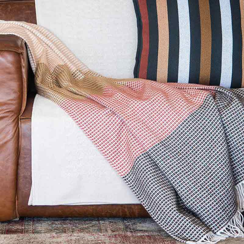 Beautuiful sustainable african throw drapped over a leather couch