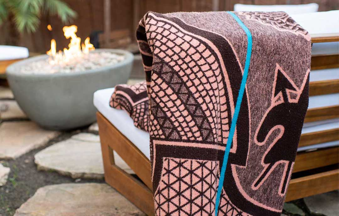 The Ultimate guide to the Basotho Heritage Blanket lesotho basotho heritage blanket over thback of a outside chair in front of a fire