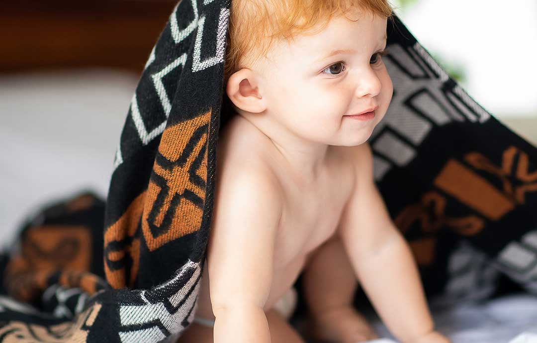 African Mudcloth design throw and blanket with baby underneath
