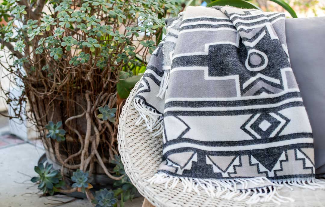 Black and white Ndebele throw over a chair in a garden