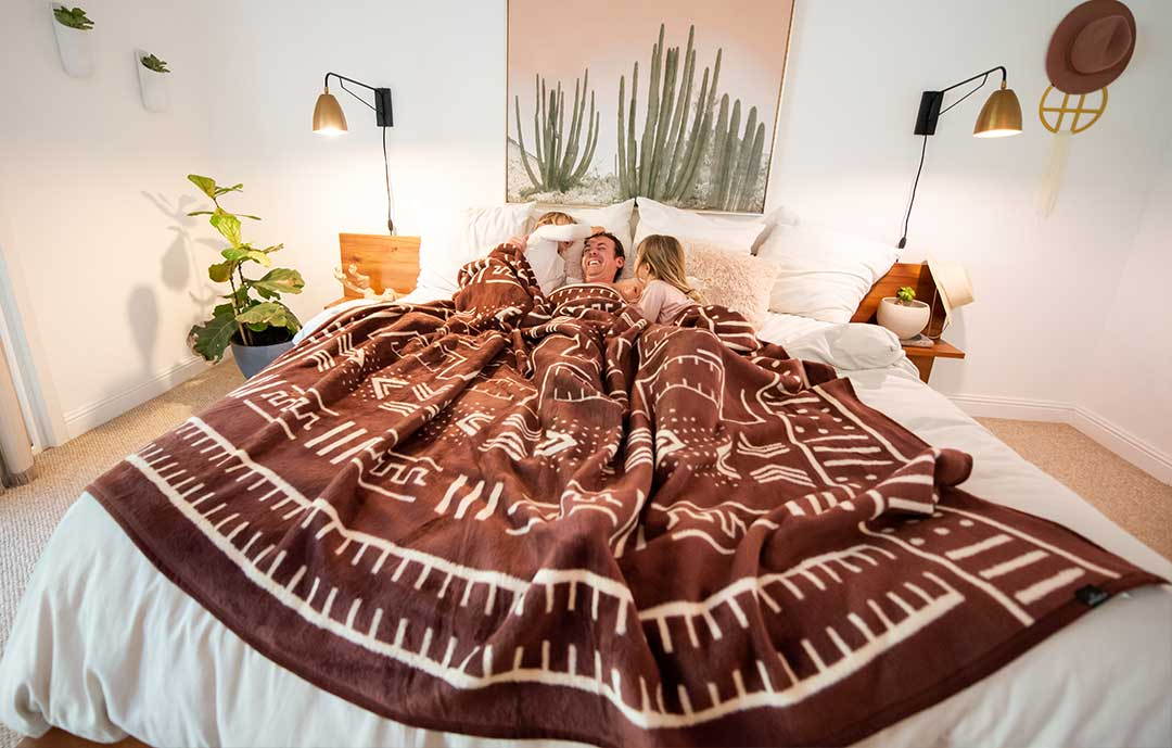 Thula Tula Mali Mudcloth blanket on king size bed with family underneath in California decorated room