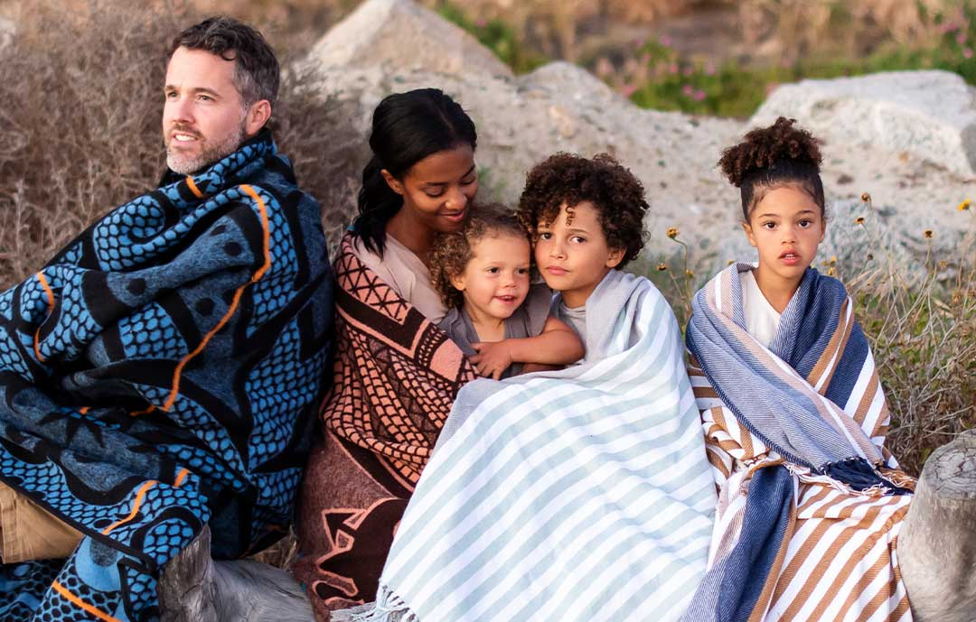 Family sit on beack wrapped in baotho blankets
